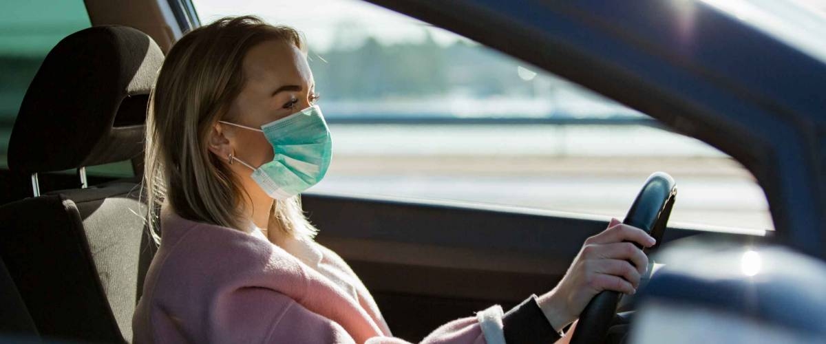 Woman in protective mask driving a car on road.