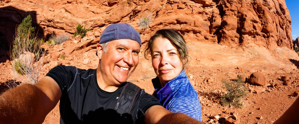 Older couple hiking near red rocks