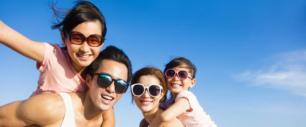 Family wearing sunglasses and having fun at the beach