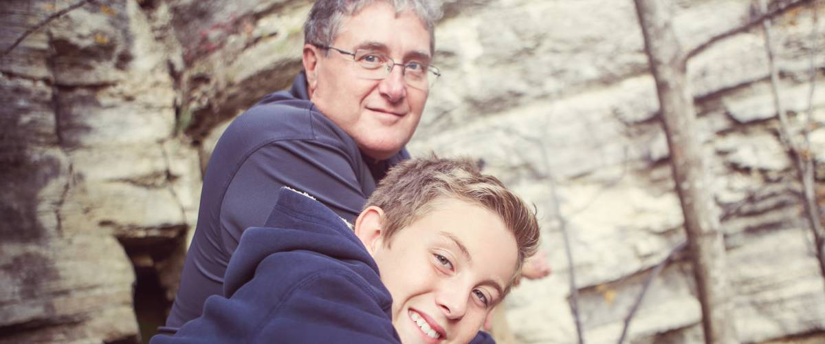Father and son in front of a rock wall