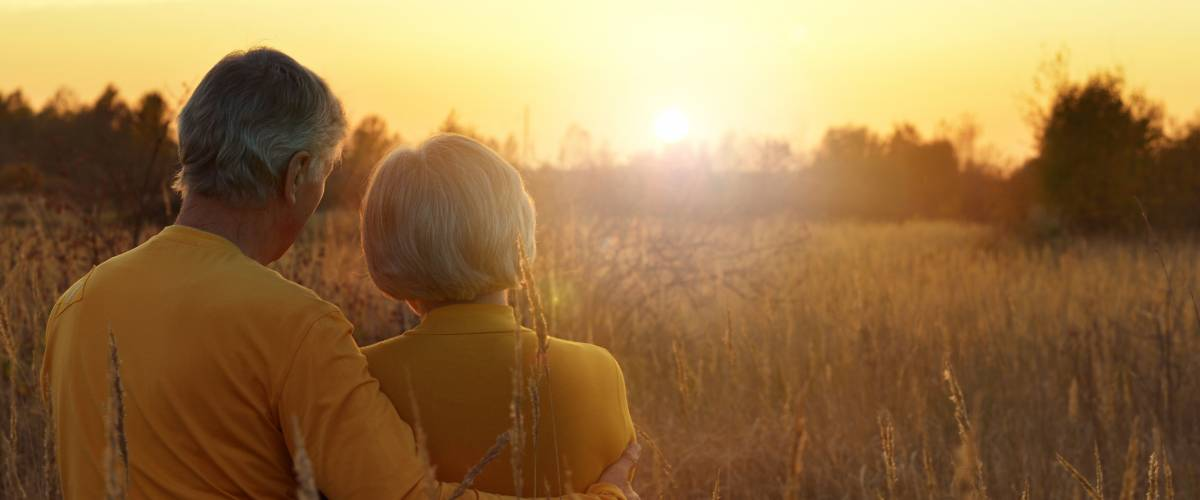 Older couple in a wheat field at sunset