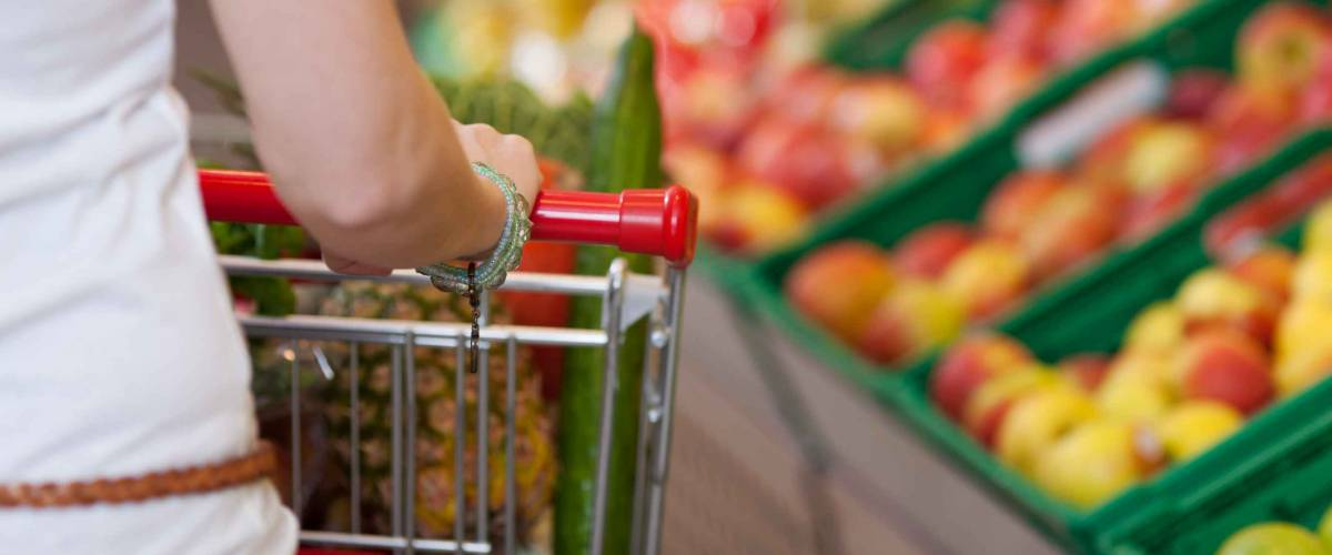 Cropped image of young woman pushing shopping cart in grocery store