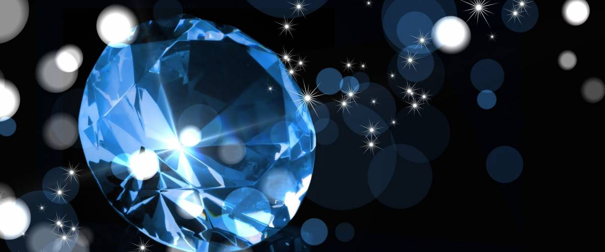 Blue diamond on black background. Around the diamond a lot of lights and glitter. Luxurious backdrop for an expensive gift.