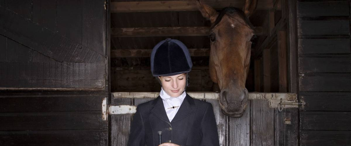 Young female horseback rider with horse and dog in the stable