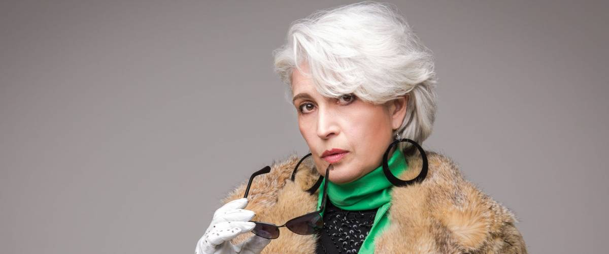 Portrait of senior rich woman holding sunglasses in front of her. Vogue lady in fur coat posing in studio isolated on grey background.