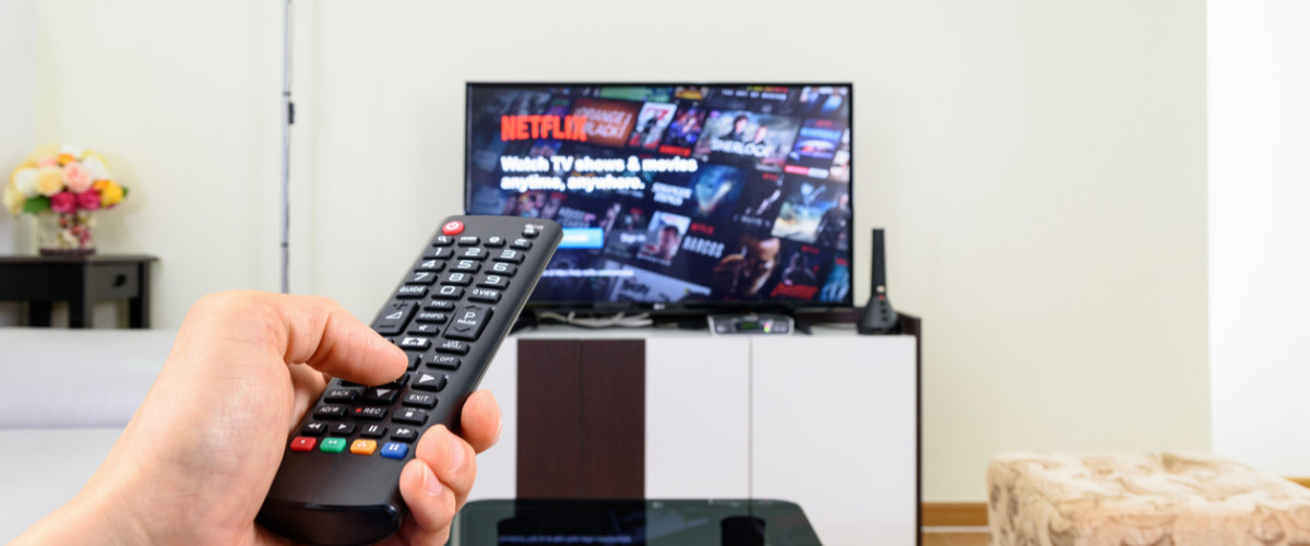 Netflix on a television with remote in foreground
