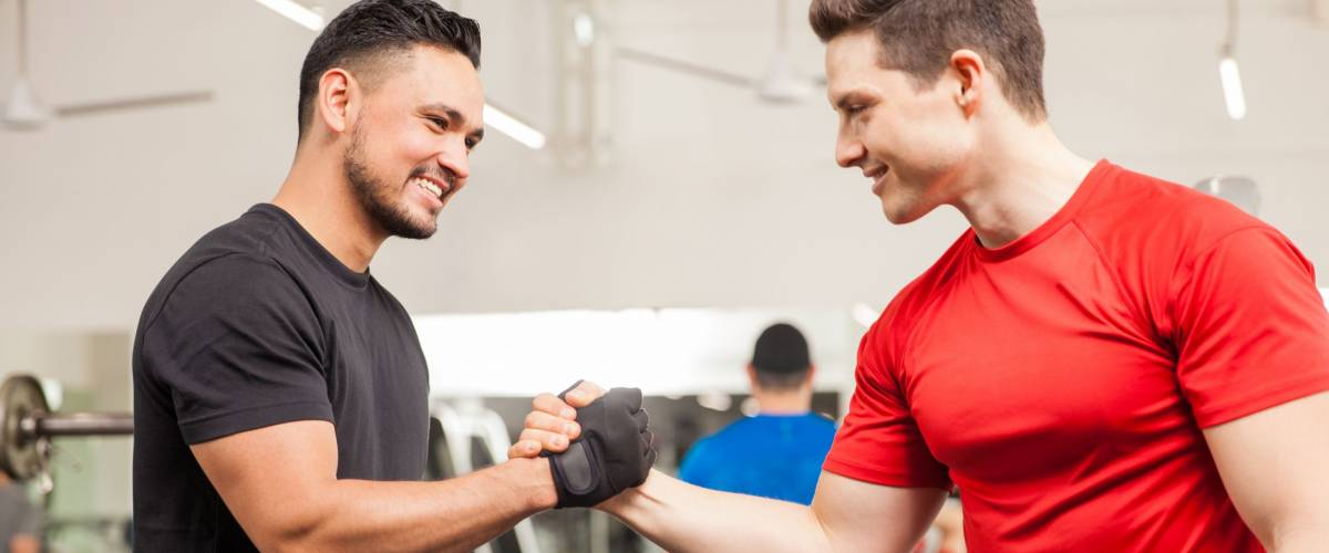 Two young men meeting at the gym and giving each other a handshake