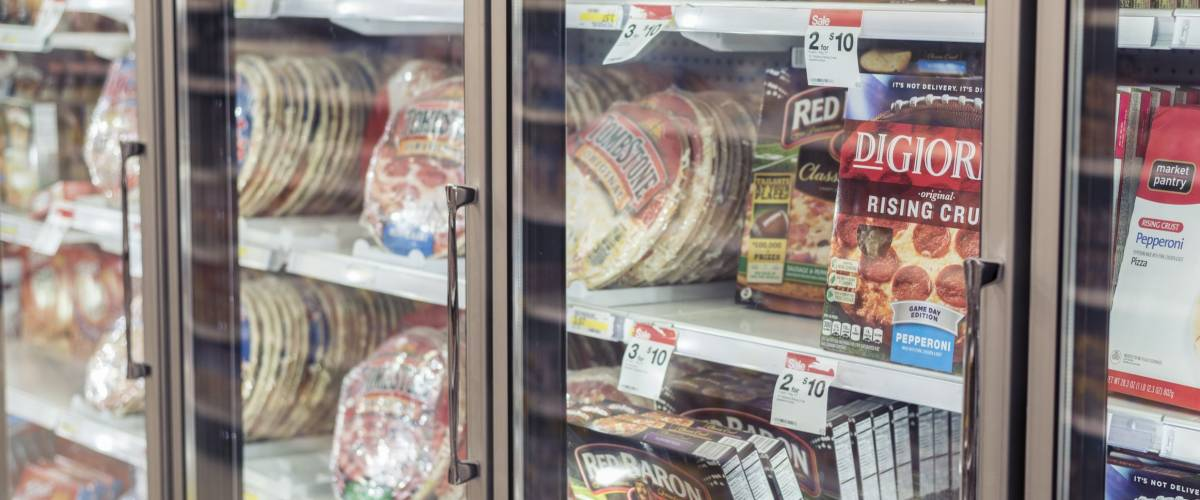 Moorhead, Minnesota, United States - December 7, 2015: Freezer full of pizza in local supermarket, seen through the glass.