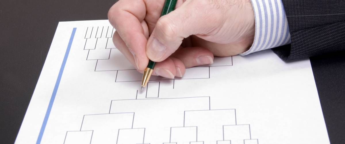 A businessman's hand holding pen completing March Madness bracket