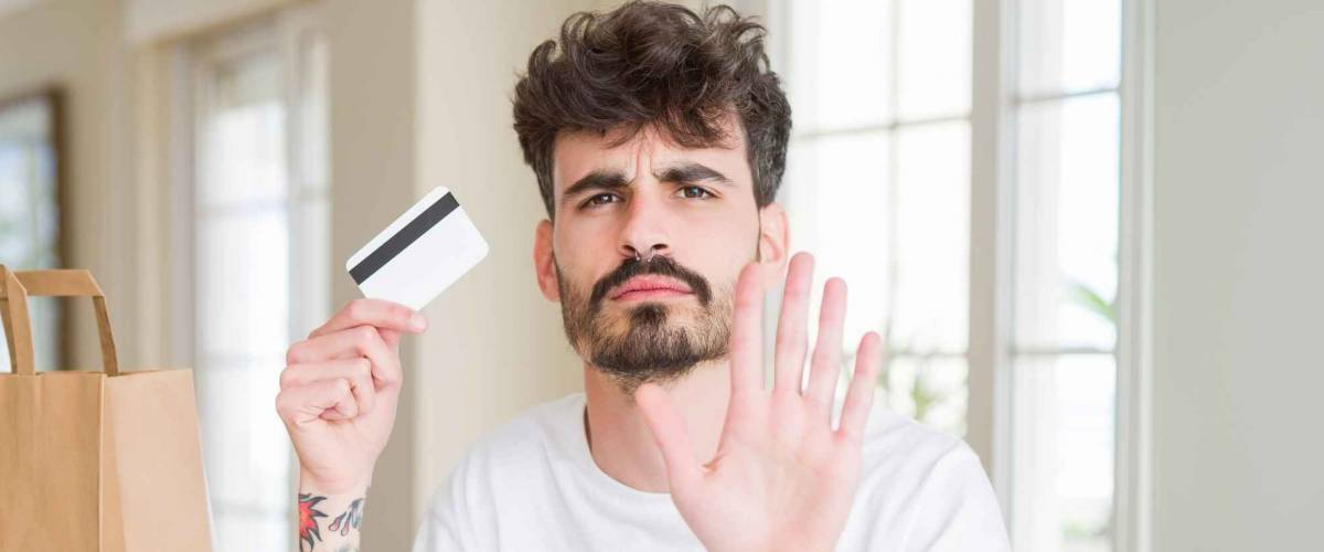 Young man eating asian sushi from home delivery using credit card as payment with open hand doing stop sign with serious and confident expression, defense gesture