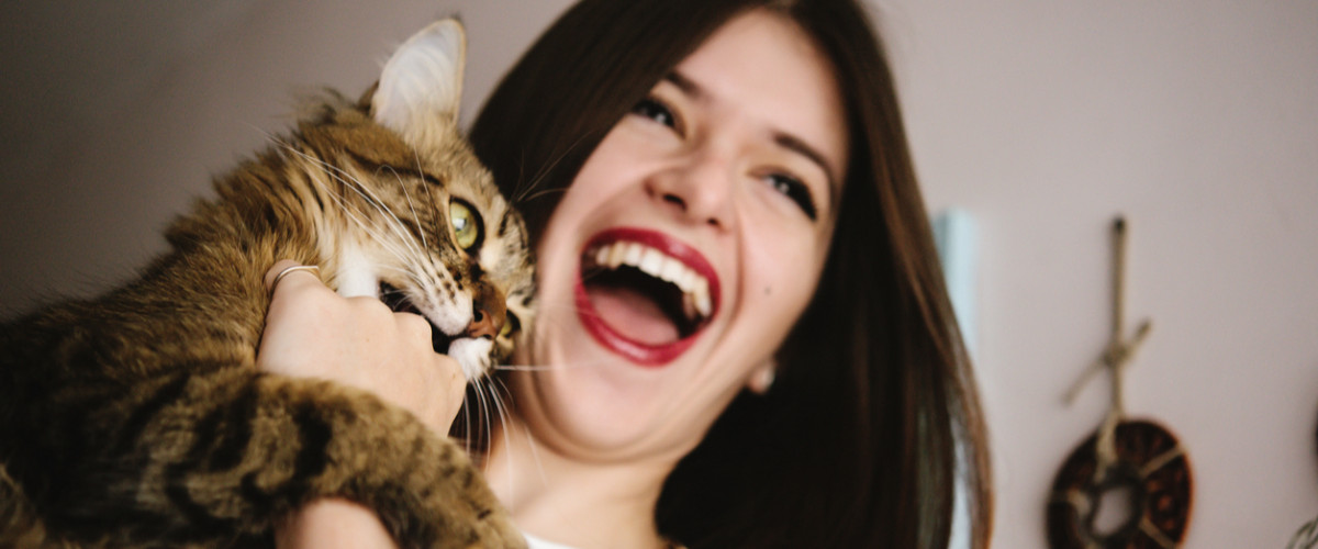 Woman smiling holding a cat