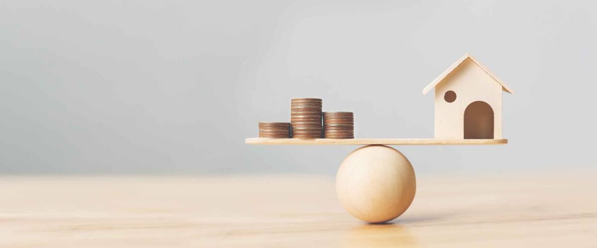 Wooden home and money coins stack on wood scale. Property investment and house mortgage financial real estate concept