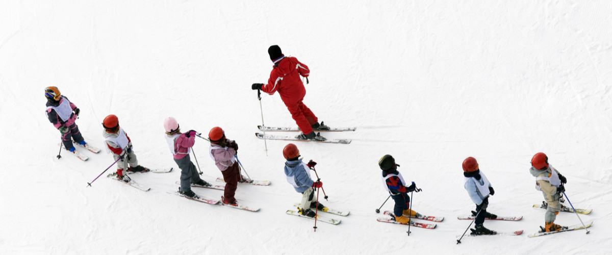 Skiing lessons students and their teacher