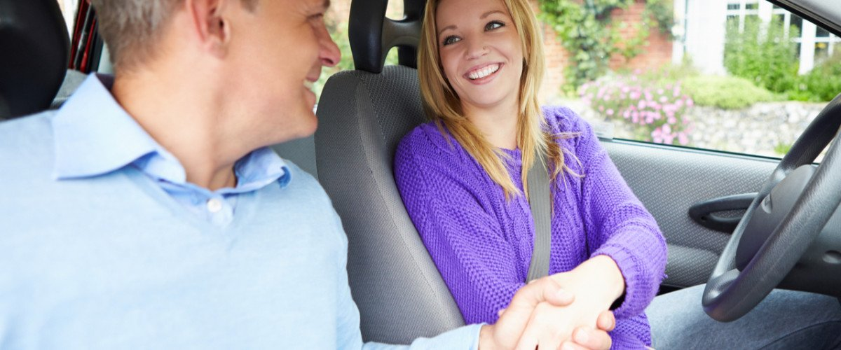 Young woman and man shaking hands inside a car