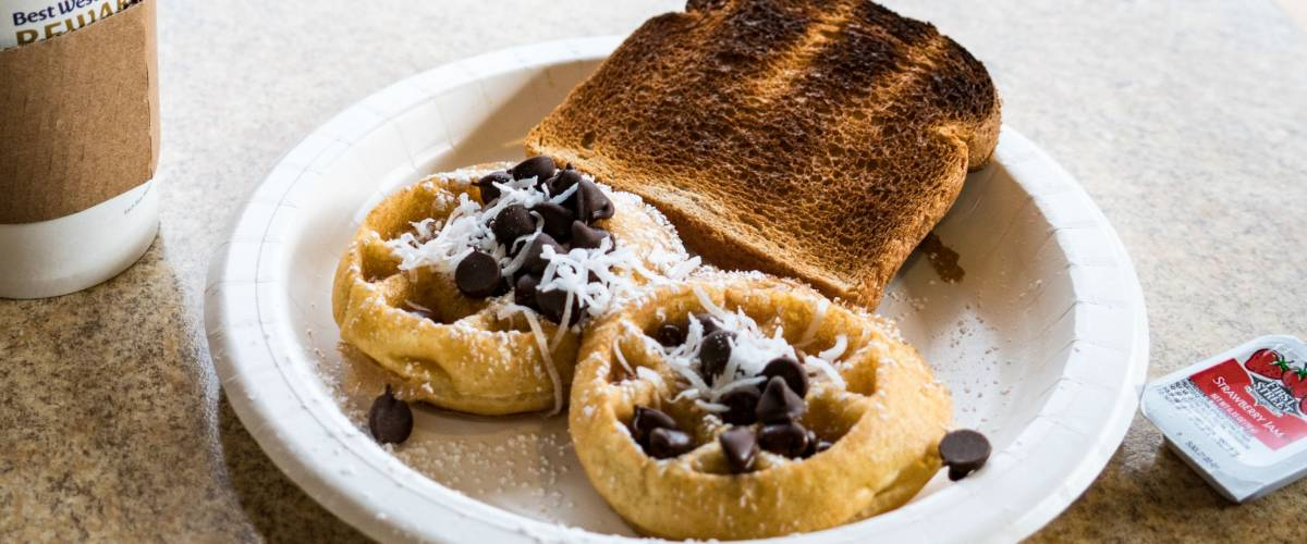 OCT 20 2017 - MORRO BAY, CALIFORNIA: A typical hotel breakfast at a Best Western motel, with coffee, toast, waffles with toppings and jelly, sitting on a table