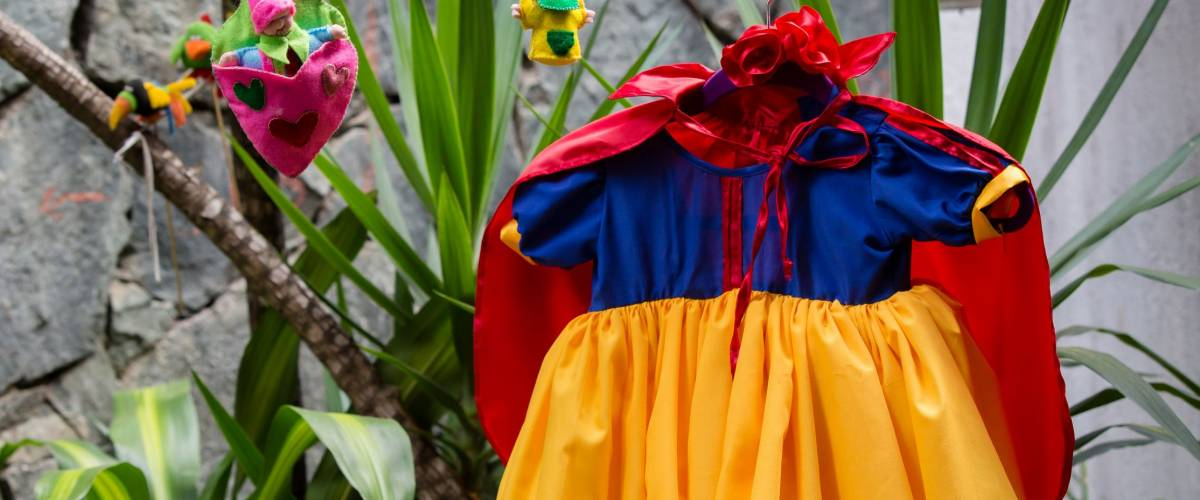 Concept: Trick or Treat. Getting ready for a kids costume party. Little snow whites dress hanging in the backyard. Halloween kids costume party.