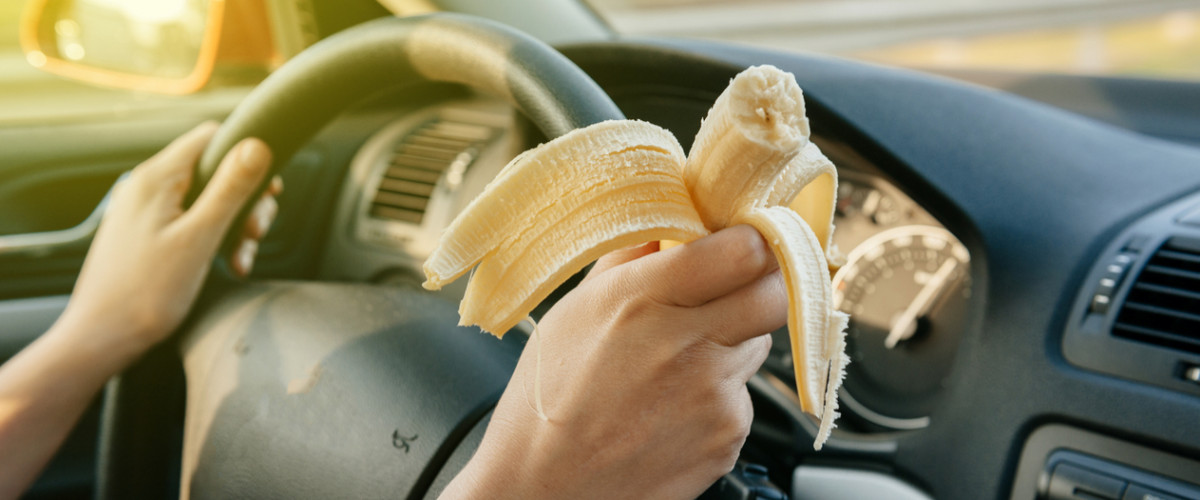 Woman eating a banana while driving a car