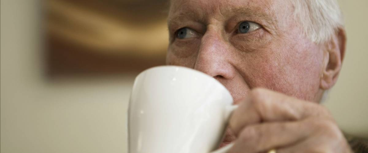 Closeup of elderly man drinking coffee while looking away