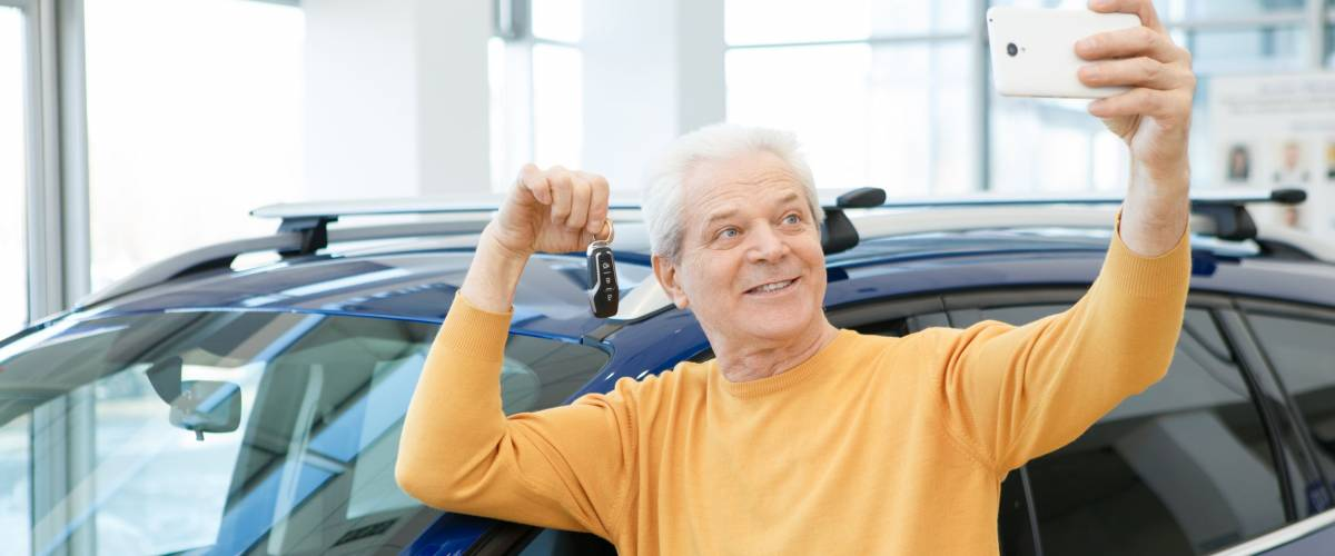Joyful senior man smiling taking a selfie with car keys to his new auto
