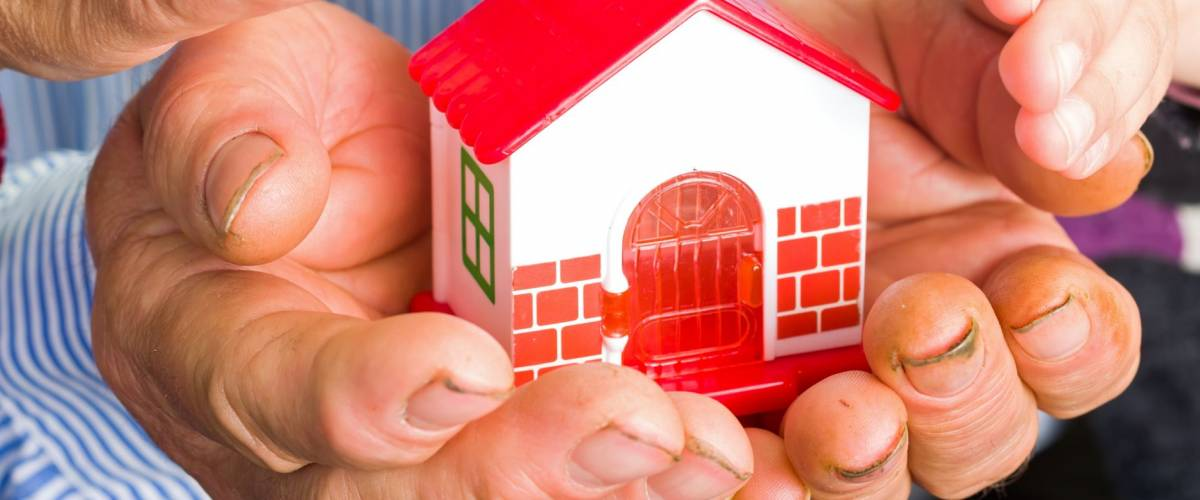 Photo of a miniature house holding in hands