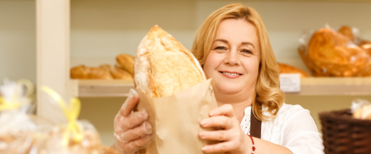 Woman handing bread over counter in bakery