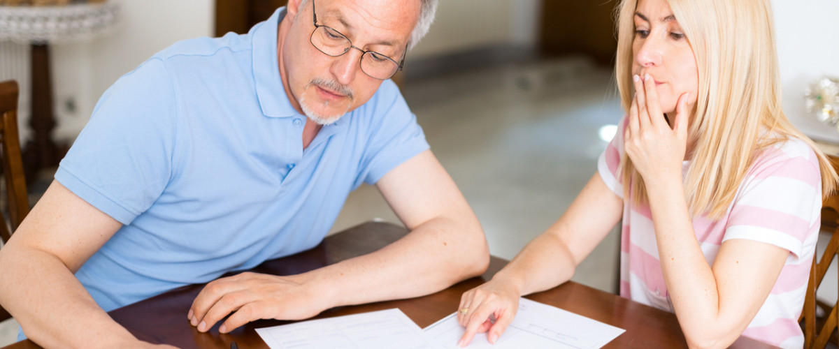 Mature couple looking at and discussing personal finances