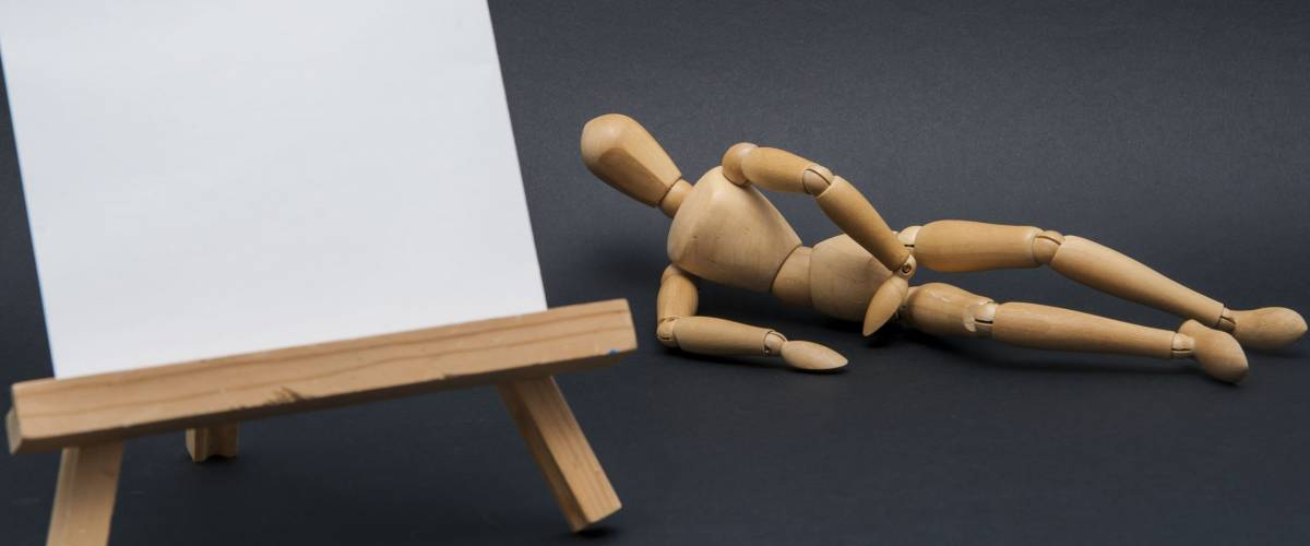 Painting a model/Painting easel with a fresh new white canvas on prepared for painting and a model in the out of focus background represented by a wooden dummy.