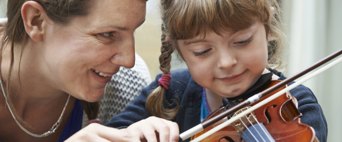 Woman tutoring a young girl on violin lessons