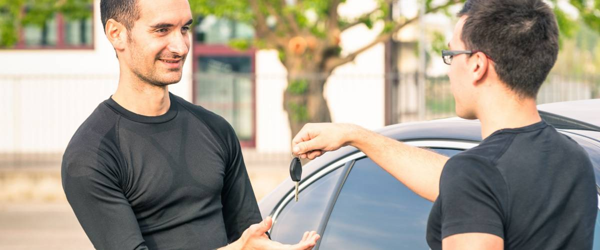 Happy satisfied young man receiving car keys from owner