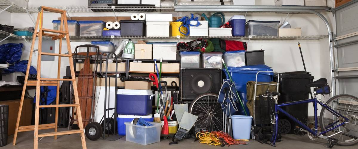 Suburban garage mess.  Boxes, tools and toys in disarray.