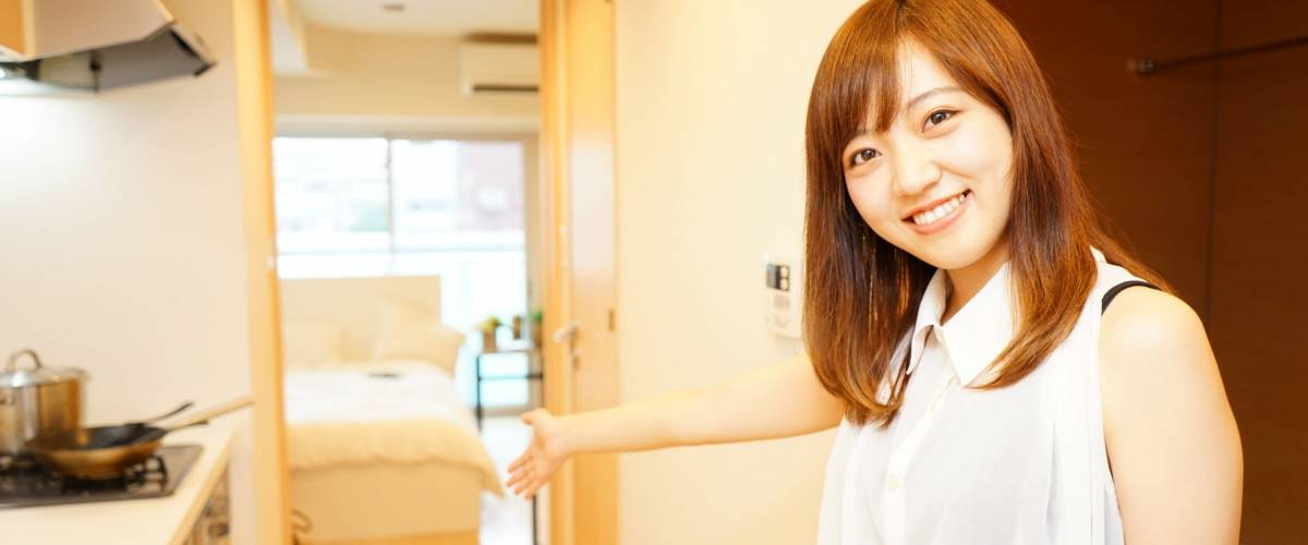 Young Japanese girl inviting her friend to her single living room with light design
