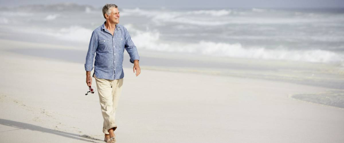 Senior man walking on beach
