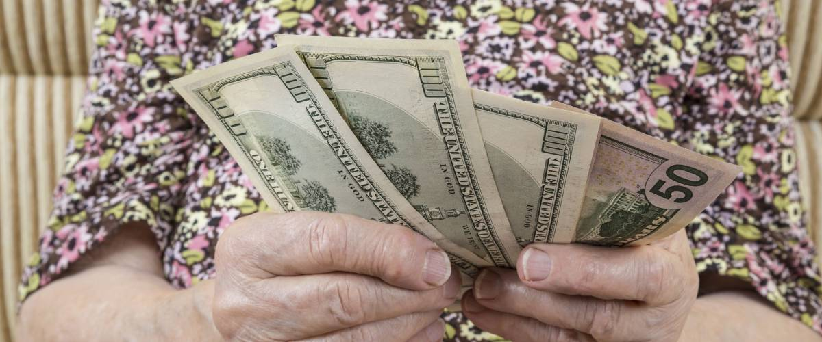close up hands of a senior woman holding money