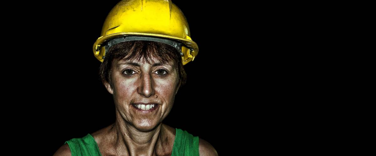 Mature adult woman in hard hat, protective safety headgear. Underground. Gritty.