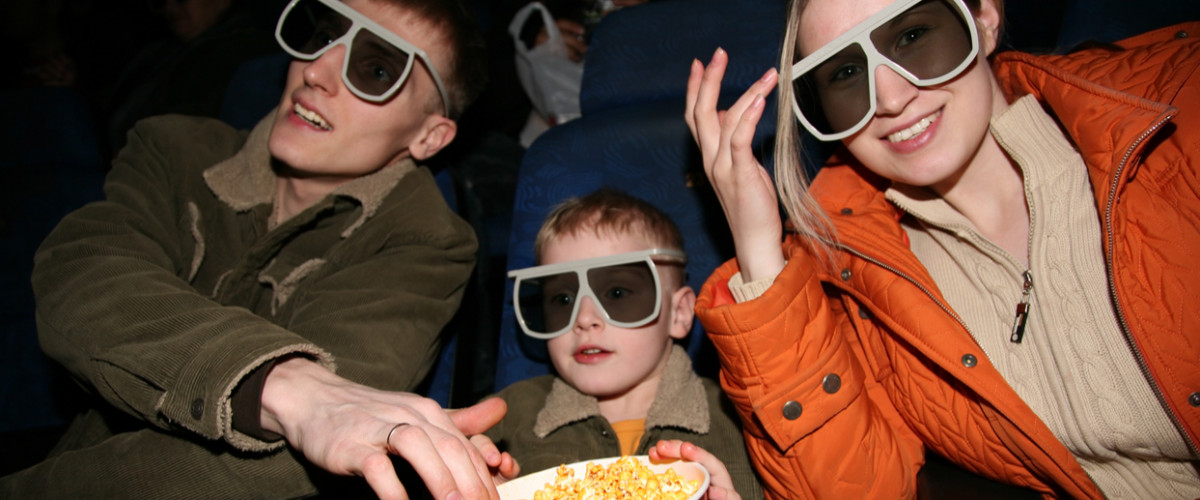 Happy young family at movie theatre