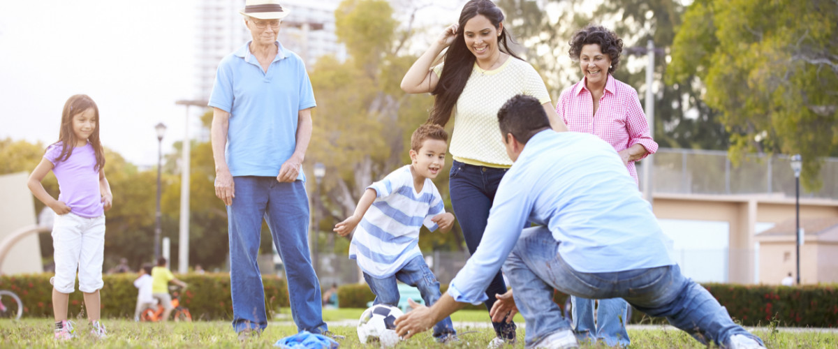 Multi-generational family playing soccer in the park