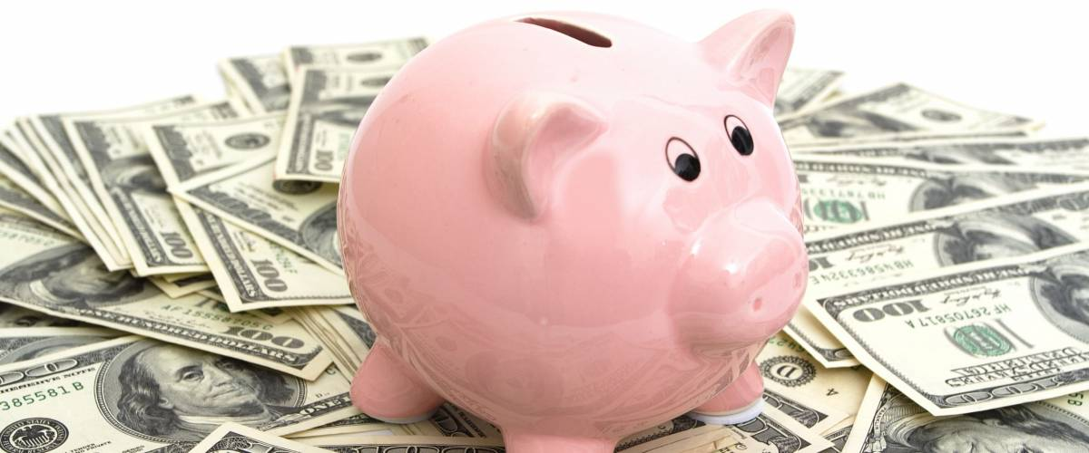 pink piggy bank sitting on top of hundred dollar bills