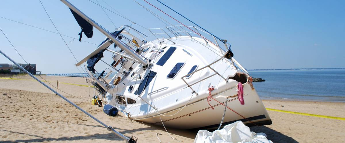 NORFOLK, VIRGINIA - AUG 28: A sailboat lies damaged on the beach on August 28, 2011 in Norfolk, Virginia a day after Hurricane Irene hit the area on Aug. 27, 2011.