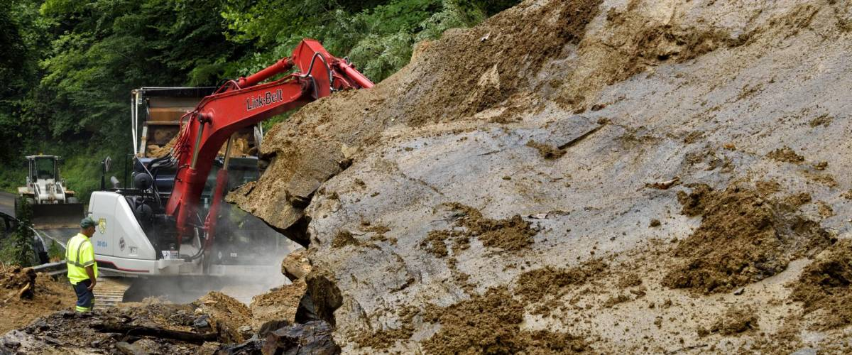 West Virginia Department of Highways workers seek to open highway closed by flashflood caused landslide in Nicholas County, West Virginia, USA on July 13, 2015