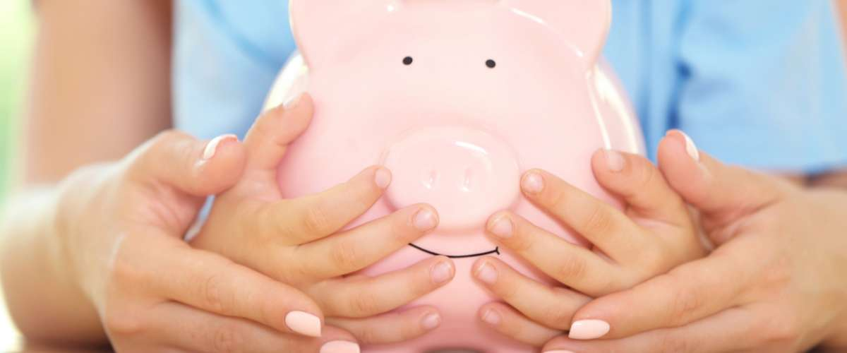 Savings concept. Mother and son hands holding piggy bank, close up