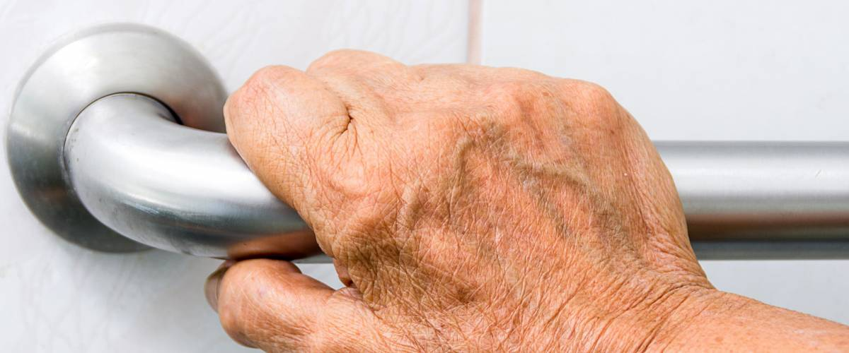 elderly holding a grab bars in a bathroom