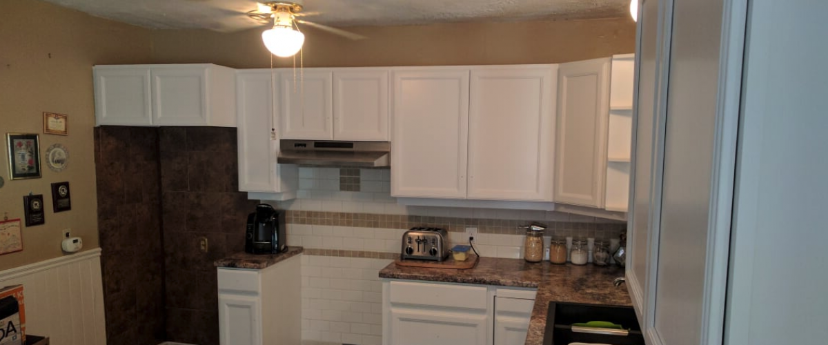 Poorly decorated dark kitchen with missing stove.