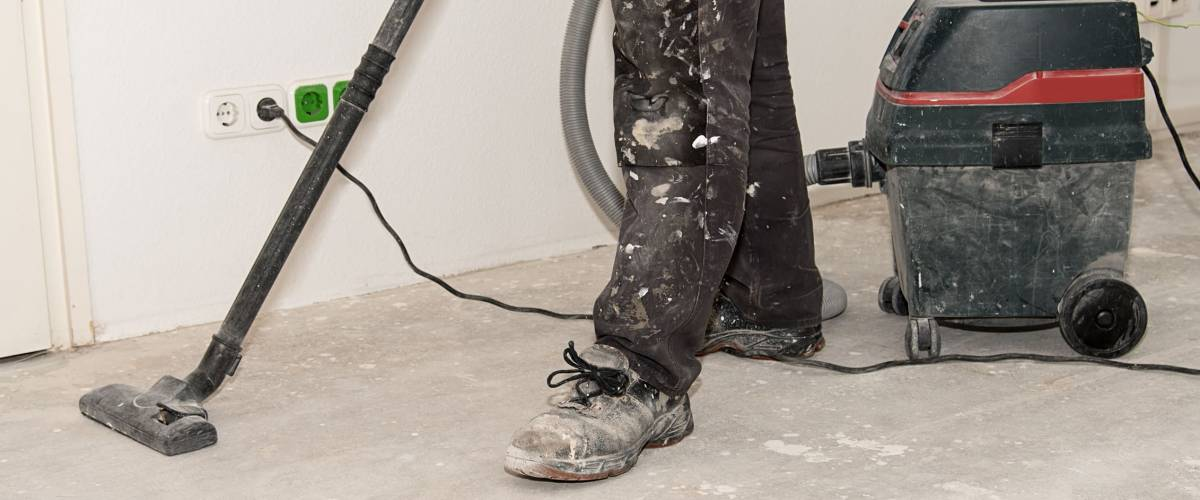 Worker man use vacuum cleaner in construction
