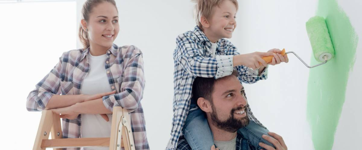 Happy family renovating their new home, the father is piggybacking his son and helping him painting with a roller, the mother is smiling and standing on a ladder