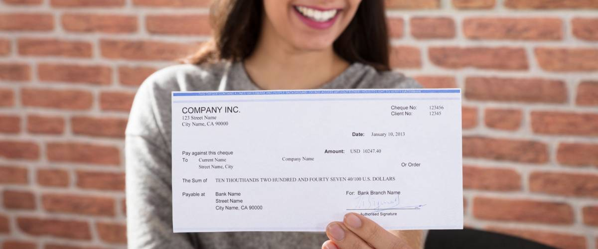 Close-up Of A Smiling Woman Showing Company Cheque