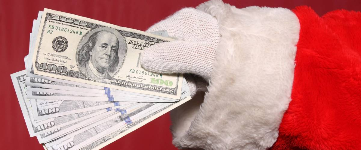 Santa Claus holds Christmas Cash. American Money in Santa's Hand.