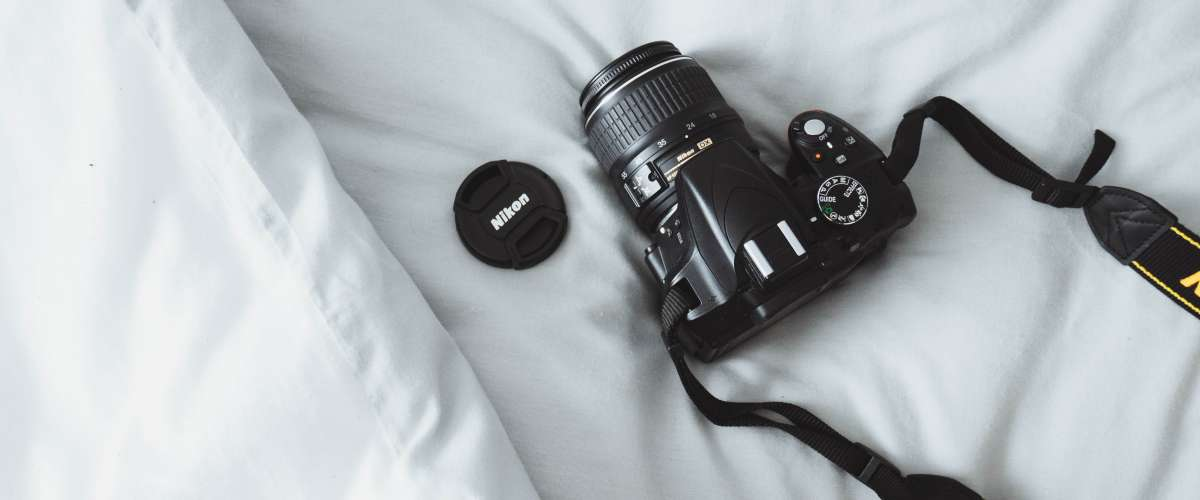 DSLR camera on white bed sheets