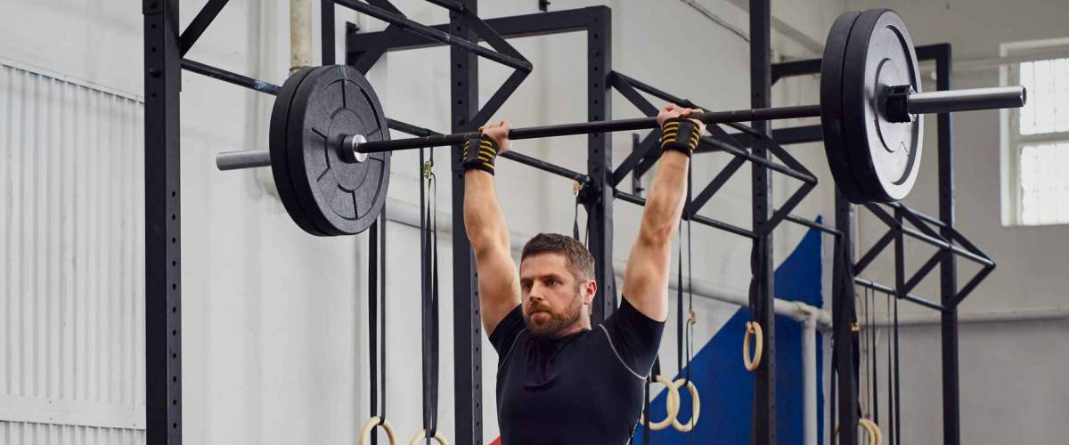Muscular man training lunges with barbells over head