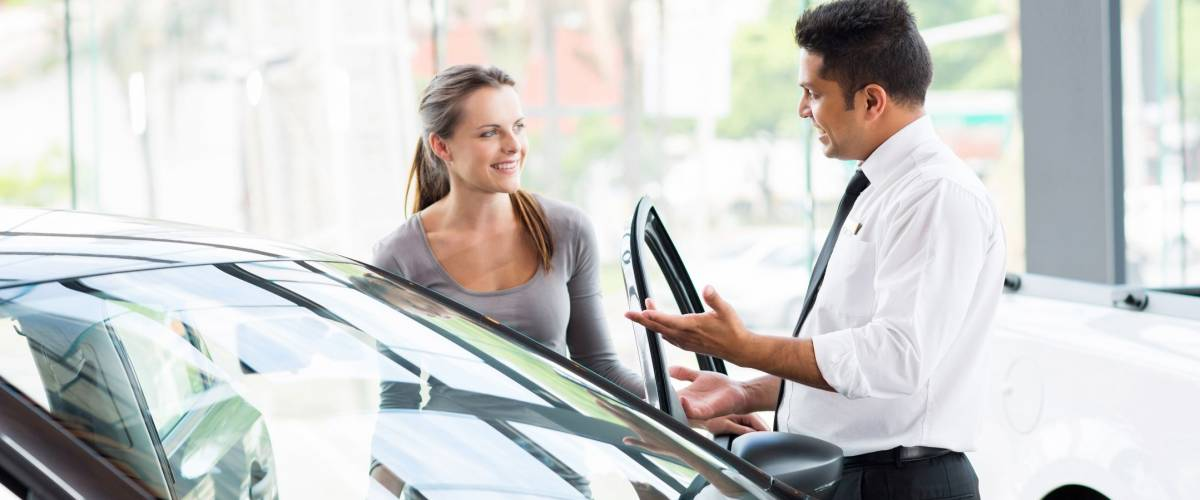 friendly vehicle dealer showing young woman new car