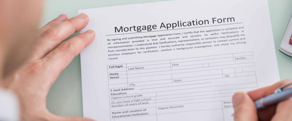 Close-up Of Person Holding Pen in Hand Over Mortgage Application Form